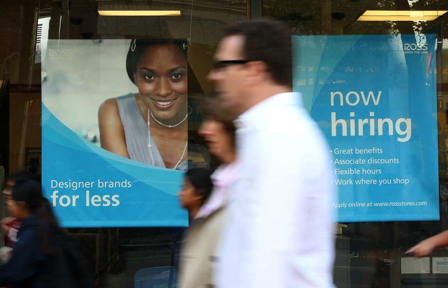 Pedestrians walk by a now hiring sign that is posted in the window of a Ross Dress for Less store in San Francisco. Photo: Justin Sullivan, Getty Images