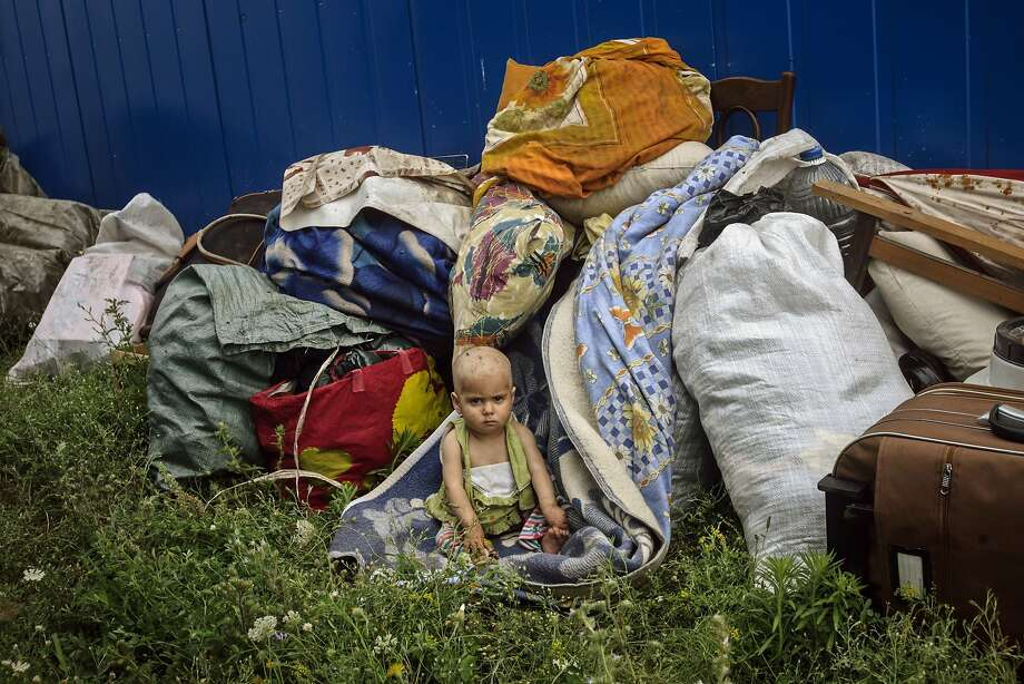 Her new home next to the dump: A Roma child sits amongst her family's belongings at a container settlement outside the Black Sea costal town of Eforie, Romania. Local authorities relocated eight Roma families, including 19 small children, from a building they were using as shelter in Eforie to the container settlement outside the city limits. Human rights organizations immediately protested the move, as it lacks running water and electricity, and sits next the a garbage dump. Photo: Bogdan Chesaru, Associated Press