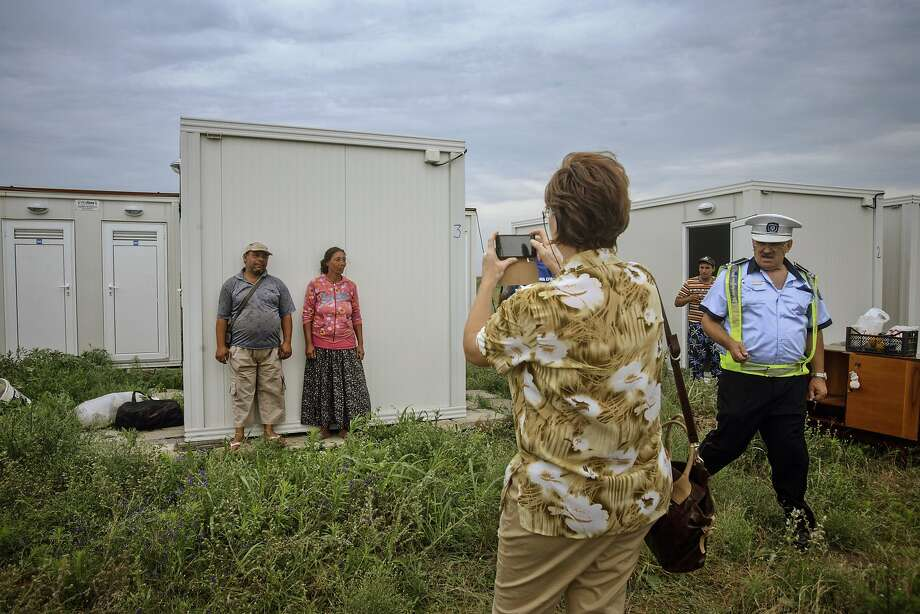 A Roma couple, top left, pose next to their new home in a shipping container outside Eforie, a Romanian coastal town along the Black Sea. Photo: Bogdan Chesaru, Associated Press