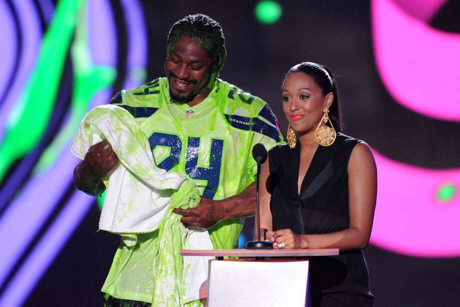 Marshawn Lynch (L) and actress Tia Mowry-Hardrict speak onstage during Nickelodeon Kids' Choice Sports Awards 2014 at UCLA's Pauley Pavilion on July 17, 2014, in Los Angeles. Photo: Kevin Winter, Getty Images