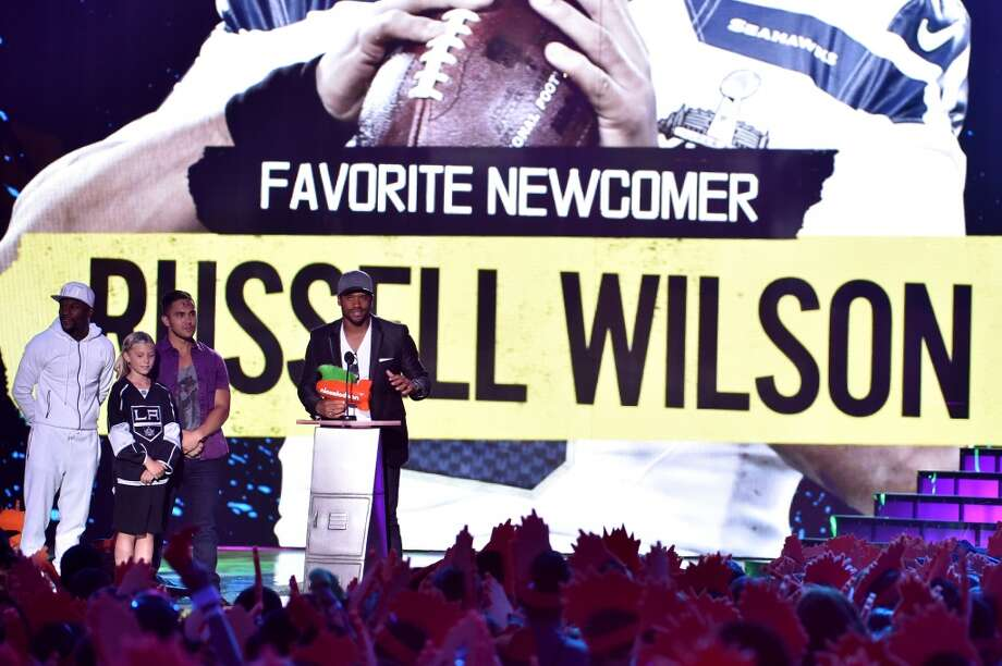 Russell Wilson accepts Favorite Newcomer from boxer Floyd Mayweather Jr. and actor Carlos PenaVega onstage during Nickelodeon Kids' Choice Sports Awards 2014 at UCLA's Pauley Pavilion on July 17, 2014, in Los Angeles. Photo: Kevin Winter, Getty Images