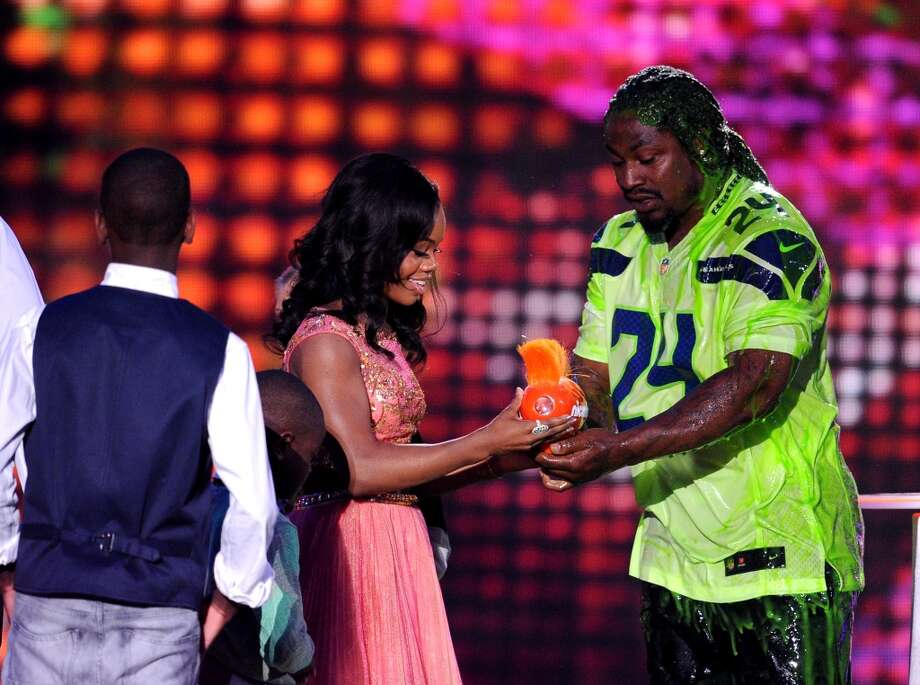 U.S. gymnast Gabby Douglas (C) accepts Queen of Swag from NFL player Marshawn Lynch (R) onstage during Nickelodeon Kids' Choice Sports Awards 2014 at UCLA's Pauley Pavilion on July 17, 2014, in Los Angeles. Photo: Kevin Winter, Getty Images