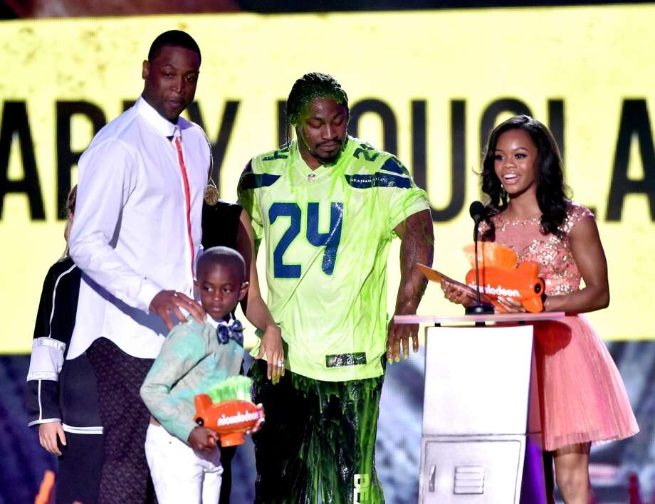 U.S. gymnast Gabby Douglas (R) accepts Queen of Swag with NBA player Dwyane Wade (L) and NFL player Marshawn Lynch (C) onstage during Nickelodeon Kids' Choice Sports Awards 2014 at UCLA's Pauley Pavilion on July 17, 2014, in Los Angeles. Photo: Kevin Winter, Getty Images