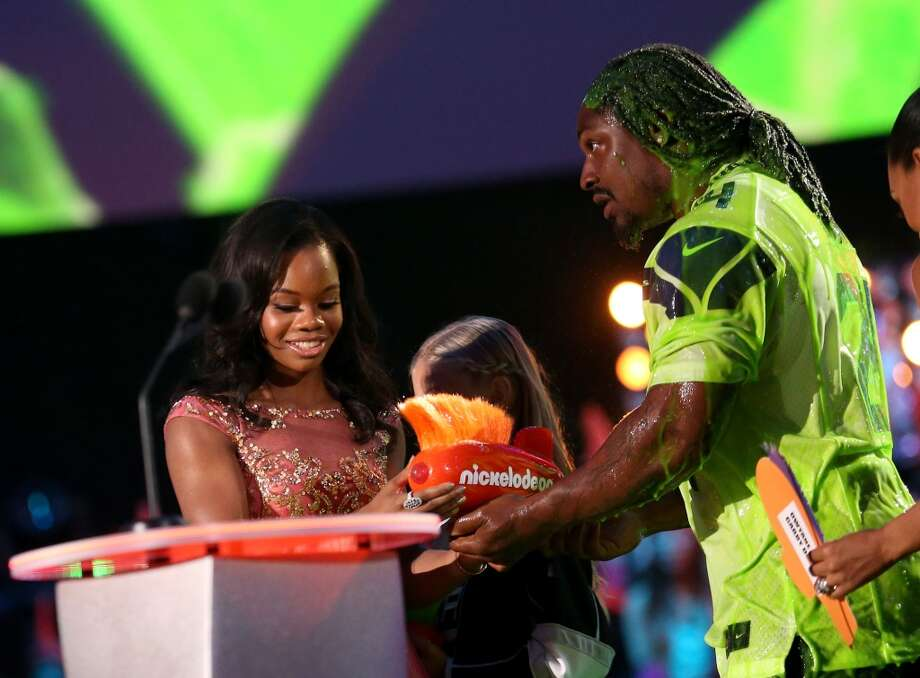 U.S. gymnast Gabby Douglas (L) accepts the Queen of Swag Award with NFL player Marshawn Lynch onstage during Nickelodeon Kids' Choice Sports Awards 2014 at UCLA's Pauley Pavilion on July 17, 2014, in Los Angeles. Photo: Mark Davis, Getty Images