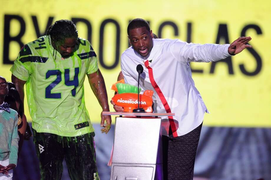 Marshawn Lynch  (L) and NBA player Dwyane Wade  speaks onstage during Nickelodeon Kids' Choice Sports Awards 2014 at UCLA's Pauley Pavilion on July 17, 2014, in Los Angeles. Photo: Kevin Winter, Getty Images