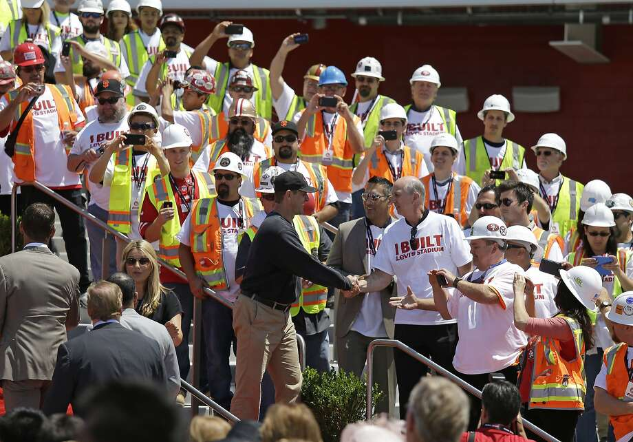 San Francisco 49ers head coach Jim Harbaugh shakes hands with construction workers just before the ribbon-cutting ceremony Thursday. Photo: Eric Risberg, Associated Press