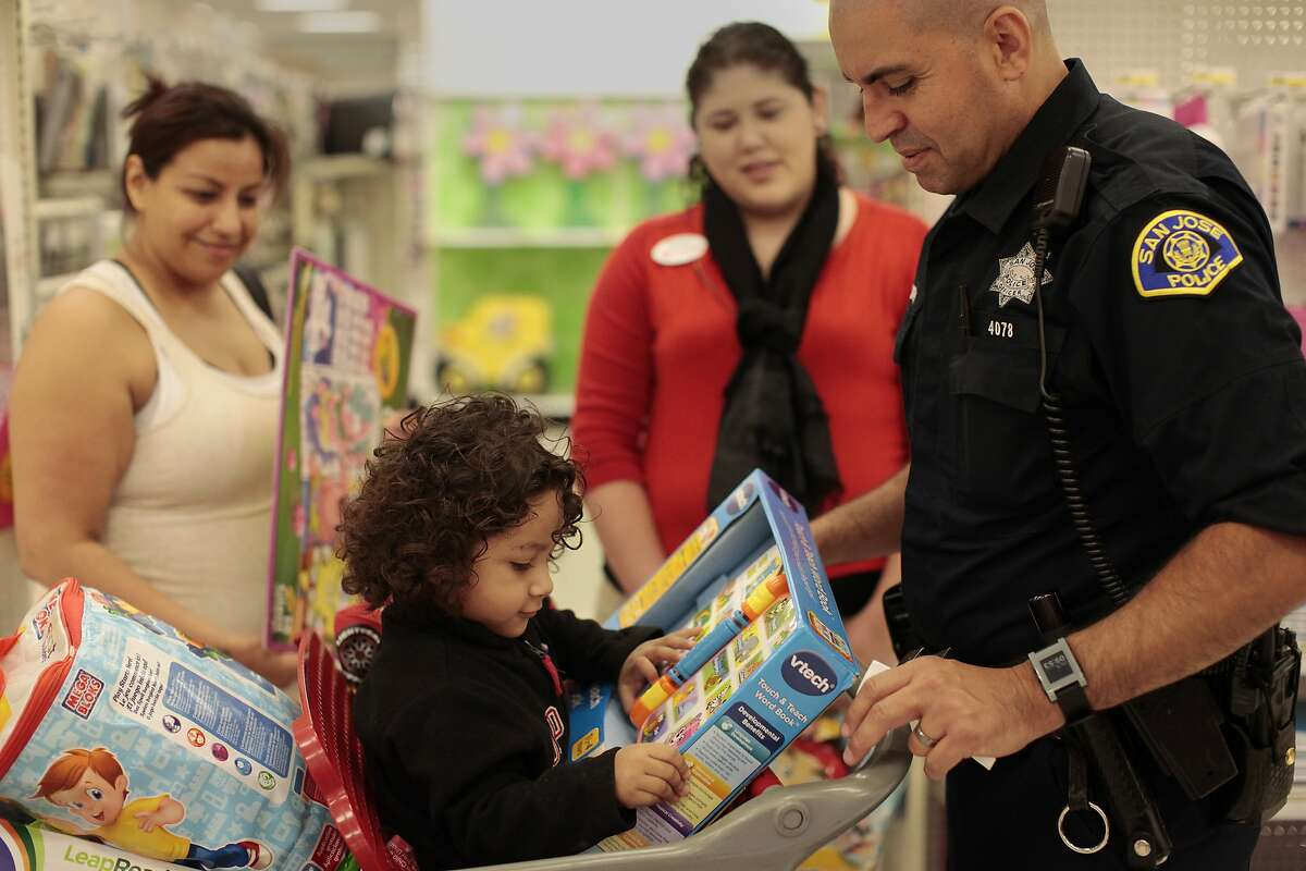 Officer Eduardo Sandoval looks over a new toy with Joseph Cortez, 2, at Target on Friday, July 19, 2014 in San Jose, Calif. The Shop with a Cop Silicon Valley Foundation took the Alejo family, who lost a mother recently, and others through target to shop for school supplies and clothes with law enforcement.