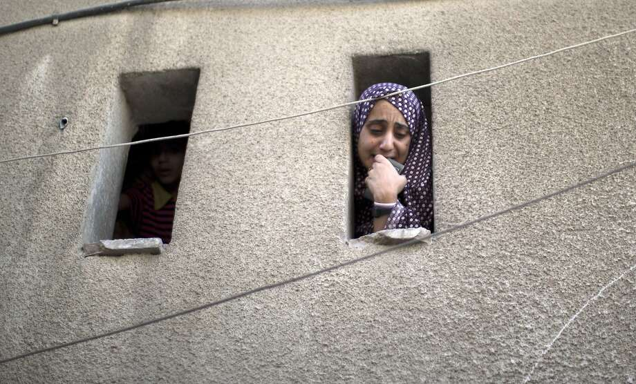 A Palestinian woman weepsas she watches the funeral of Rani Abu Tawila, a Palestinian killed in an Israeli attack, from the window of a house in Gaza city. Israel warned it could broaden a Gaza ground assault aimed at smashing Hamas' network of cross-border tunnels. Photo: Mahmud Hams, AFP/Getty Images