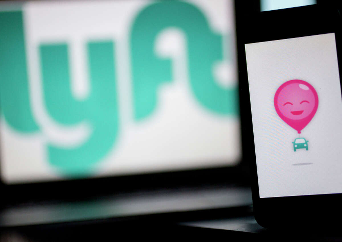 The Lyft Inc. logo and application (app) is displayed on an Apple Inc. iPhone 5s and MacBook Air for an arranged photograph in Washington, D.C., U.S., on Wednesday, July 9, 2014.