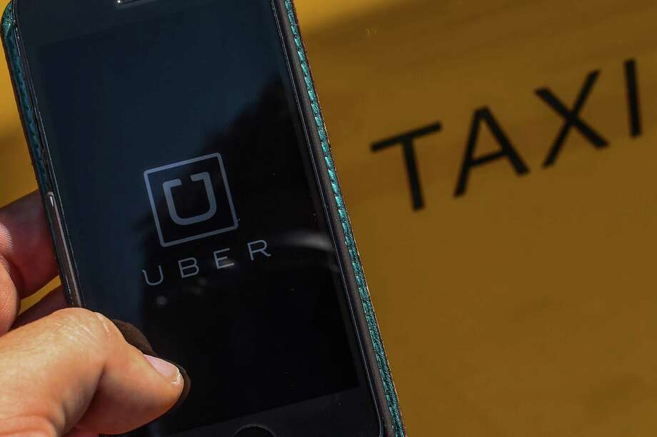 In this photo illustration, the new smart phone app 'Uber' logo is displayed on a mobile phone next to a taxi on July 1, 2014 in Barcelona, Spain. Photo: David Ramos / Getty Images / 2014 Getty Images
