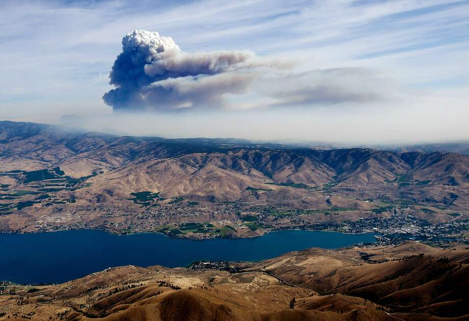 With Lake Chelan in the foreground, a large plume of smoke rises from the Carlton Complex Fire burning near Pateros. The blaze has blackened 260 square miles and destroyed 100 homes. Photo: Don Seabrook, Associated Press