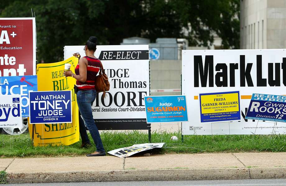 Helping the democratic process along: Judge Betty Thomas Moore moves a campaign sign for Sheriff Bill Oldham so it doesn't block her campaign sign along Poplar Avenue in Memphis, Tenn. Early voting in Shelby County began Friday. Photo: Mike Brown, Associated Press