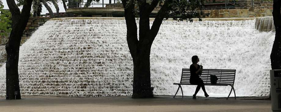 Urban waterfall: A woman cools off by a fountain in San Antonio's Hemisfair Park, which hosted the 1968 Worlds Fair. Photo: Eric Gay, Associated Press