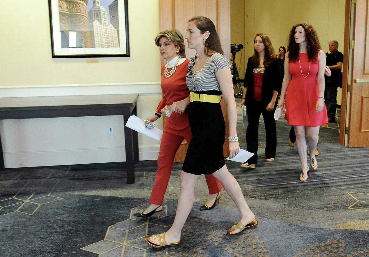 Attorney Gloria Allred, left center, leaves a news conference with Kylie Angell, center, Erica Daniels, second from right, and Rosemary Richi, right, Friday, July 18, 2014, in Hartford, Conn. The University of Connecticut will pay nearly $1.3 million to settle a federal lawsuit filed by five women who claimed the school responded to their sexual assault complaints with indifference, the two sides announced Friday.