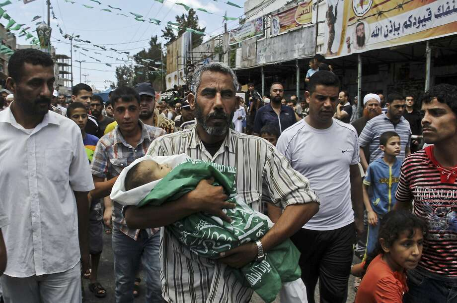 A Palestinian relative carries the body of 3-month-old baby Fares el-Trabeen, who was killed as his mother was wounded in an Israeli airstrike at their family home, during his funeral in Rafah, southern Gaza Strip, Friday, July 18, 2014. Minors make up almost one-fifth of those killed in Israel's 11-day bombardment of Hamas targets in densely populated Gaza, where half the population is under the age of 18. Photo: Hatem Ali, Associated Press