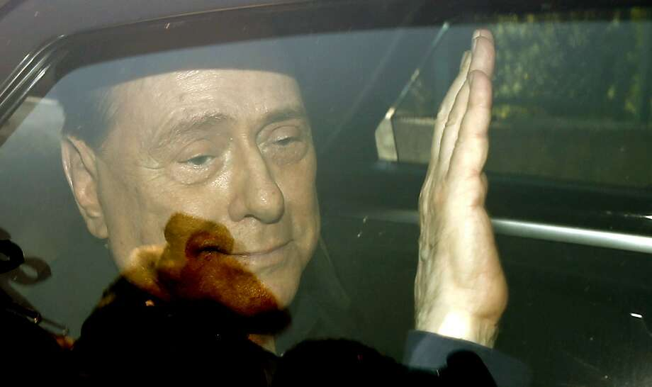 Italy's former Premier Silvio Berlusconi waves as he leaves the 'Sacra Famiglia' institute in Cesano Boscone, Italy, Friday, July 18, 2014.  An Italian appeals court has acquitted former Premier Silvio Berlusconi in a sex-for-hire case. The court's decision Friday also throws out his seven-year-prison sentence and lifetime ban on holding political office that were given to him by a lower court when it convicted him last year. Berlusconi had been accused of of paying for sex with an underage prostitute and then using his influence to cover it up. (AP Photo/Luca Bruno) Photo: Luca Bruno, Associated Press