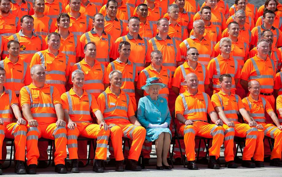 They've been working on the railroad: Queen Elizabeth II poses with construction workers during the official opening of the refurbished Reading Train Station facilities west of London. Photo: Ben Gurr, AFP/Getty Images