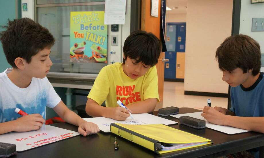 From left, Santiago Noriega, Jason Lee-Amezcua and Kevin Formento work on an equation during the Bridge to Algebra 8 class on Thursday, July 17 at Central Middle School. Photo: Paul Schott / Greenwich Time