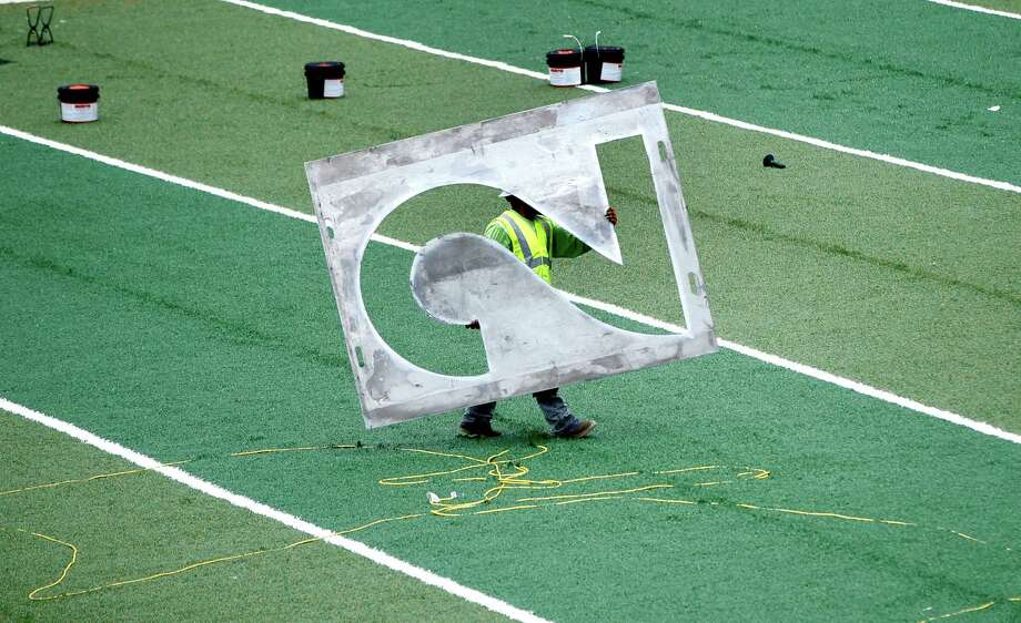 A worker with UBU Sports hauls a stencil of a number two across the newly installed turf during installation of the turf at University of Houston's John O'Quinn Field at TDECU Stadium, Friday, July 18, 2014, in Houston. Photo: Karen Warren, Houston Chronicle / © 2014 Houston Chronicle