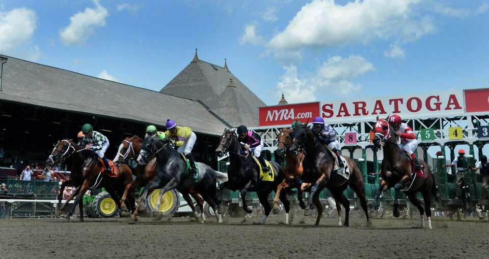 Horses break the gate for the first race of the 2014 Saratoga Race Course meeting Friday afternoon J