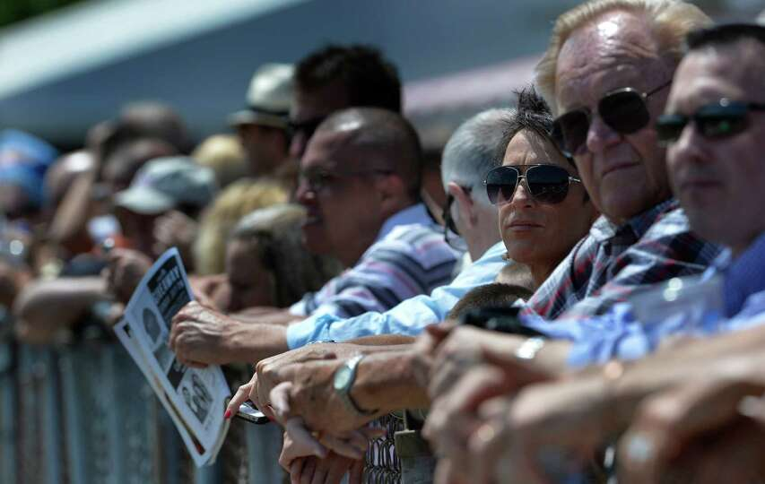 A crowd of race patrons watch the horses go to the post for the third race of opening day of the 201