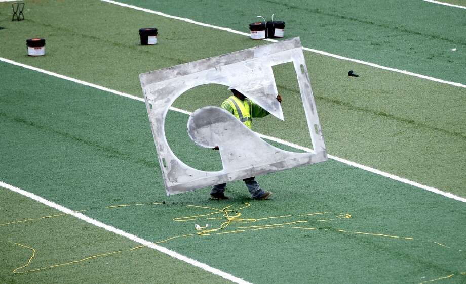 A worker with UBU Sports hauls a stencil of a number two across the newly installed turf. Photo: Karen Warren, Houston Chronicle