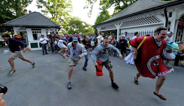 Race patrons run to snag a picnic table for opening day of the  2014 Saratoga Race Course meeting Friday morning July 18, 2014 in Saratoga Springs, N.Y.    (Skip Dickstein / Times Union) Photo: SKIP DICKSTEIN, ALBANY TIMES UNION