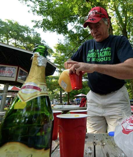 Bob Faragon of Schenectady makes some mimosa's on opening day of the 2014 Saratoga Race Course meeti