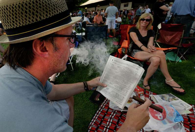 John Santulli of Westwood, N.J. exhales while handicapping the 4th race of opening day of the 2014 S