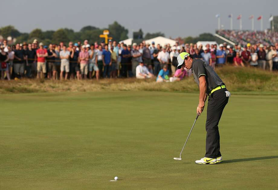 Rory McIlroy sinks a birdie putt on the 17th en route to a second straight 66 at Royal Liverpool. McIlroy leads Dustin Johnson by four strokes at the halfway point of the British Open. Photo: Scott Heppell, Associated Press