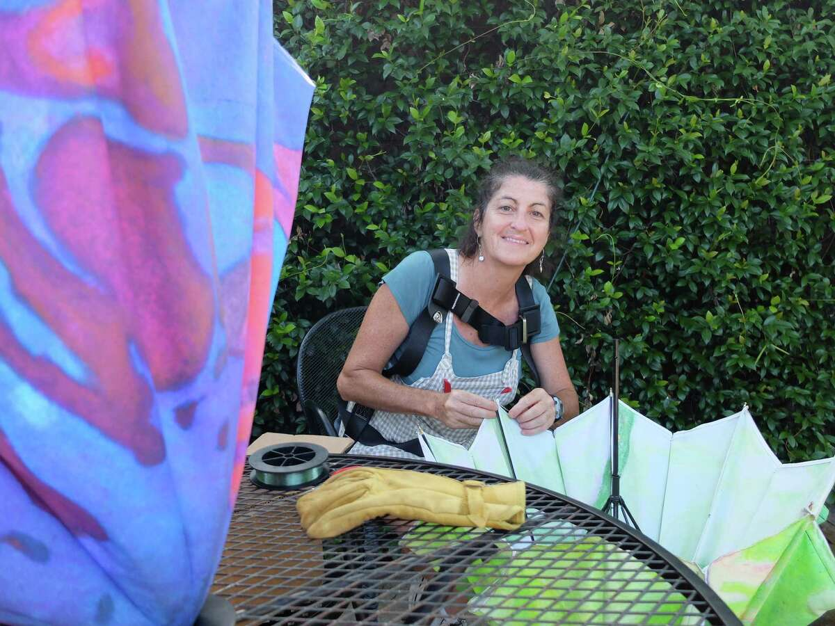"""Artist Jo Ann Fleischhauer repairs parasols for her installation """"Sexual Selection"""" at Art League Houston, on view through July 26."""