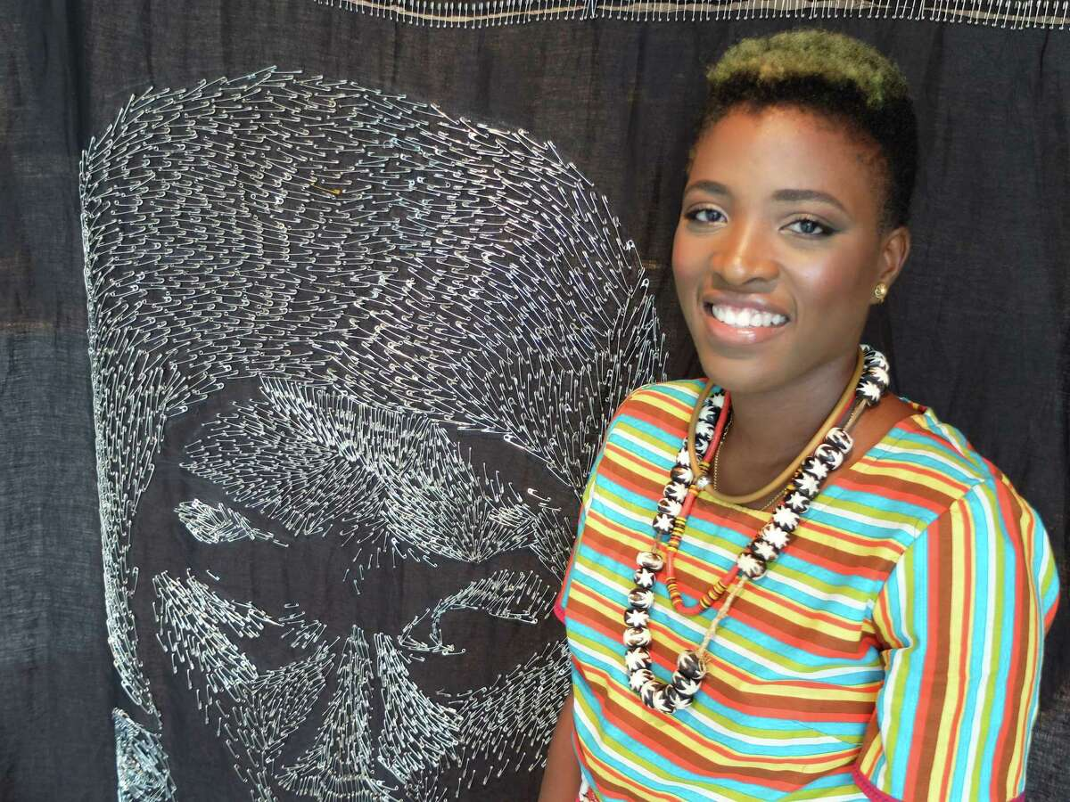 """Artist Rosine Kouamen at Art League Houston, where her solo exhibition """"Aujourd'hui, Causons Avec Nos Aieux: Intimate and Foreign"""" is on view through Aug. 1. Beside her is her tapestry """"Variation as Aberrance,"""" which features a portrait of Kouamen's grandmother from Cameroon 'drawn' with more than 1,500 safety pins."""