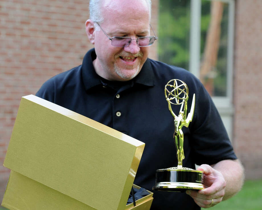 "Ken Fay holds the Emmy Award he recently received for his documentary film ""Wags 'n' Tales"", in Newtown, Conn. July 17, 2014. Photo: Ned Gerard / Connecticut Post"