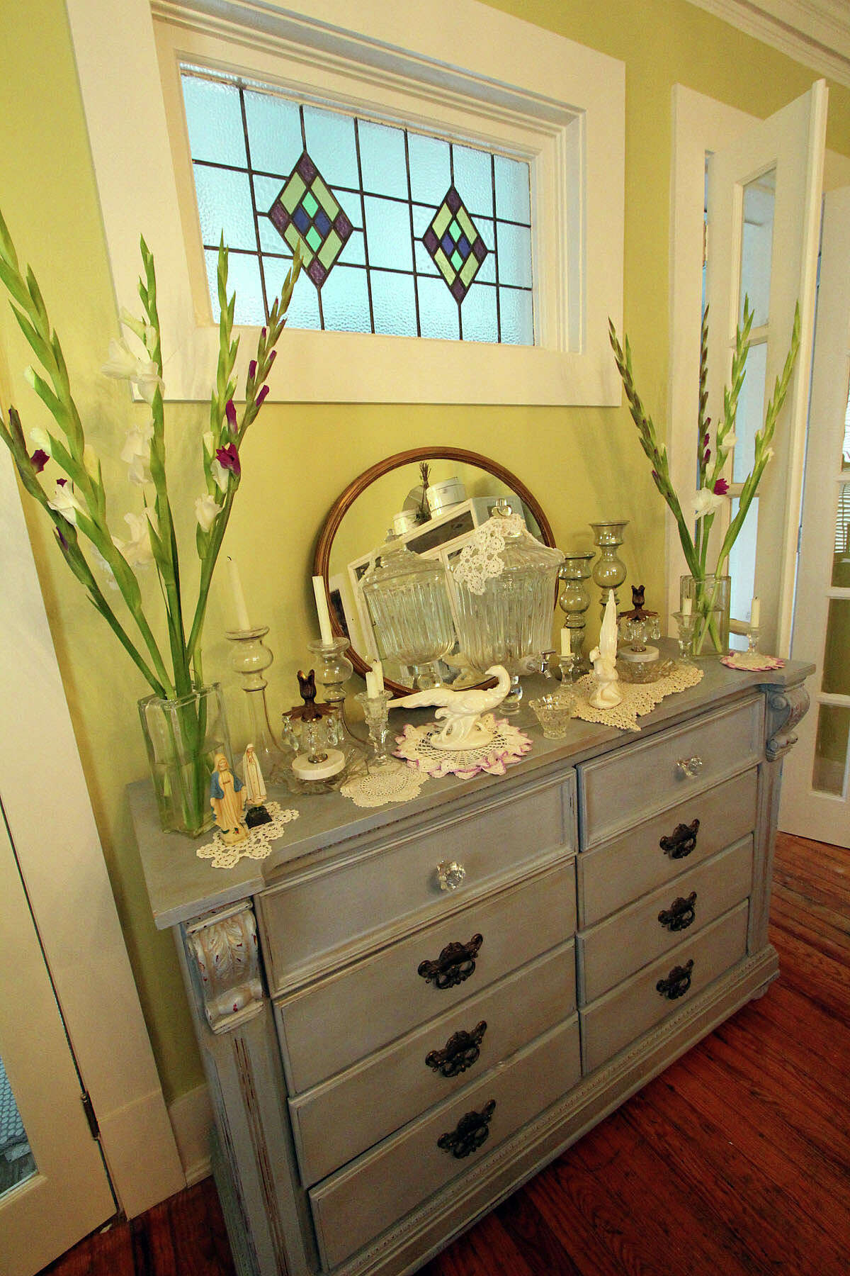 A dresser-turned-buffet, painted antique blue, sits below an original stained glass window in the dining room of the 1910 Monte Vista house Jennifer Gonzalez and Frank Garcia bought in a foreclosure sale.
