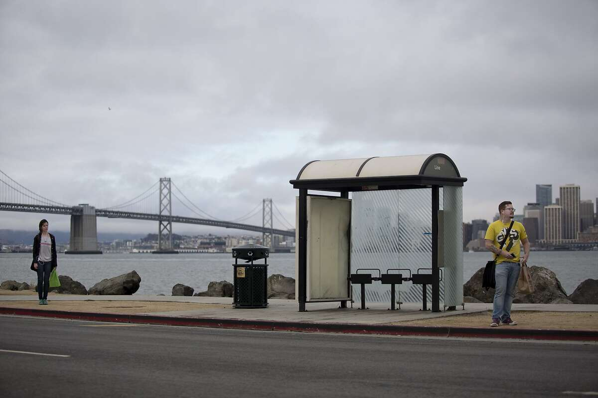 Commuters wait for bus 108 on Treasure Island, Calif. on Friday morning, July 18, 2014. By 2018, when new houses are expected to be built on Treasure Island, transportation services will increase, including a ferry to San Francisco run by the Water Emergency Transit Authority.