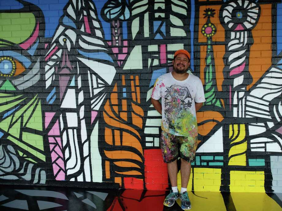 Houston street artist Daniel Anguilu poses in front of his latest mural, which covers the entry portico to the Altharetta Yeargin Museum of Art at 901 Yorkchester. Photo: Molly Glentzer