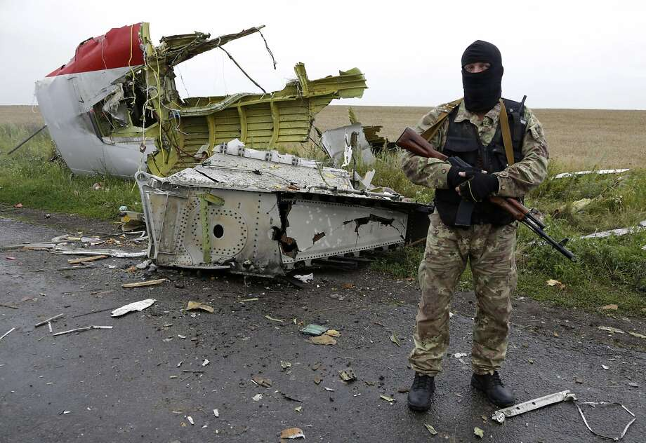 A pro-Russia fighter guards wreckage from Malaysia Airlines Flight MH17, which crashed near Hrabove, Ukraine, Thursday. Photo: Dmitry Lovetsky, Associated Press