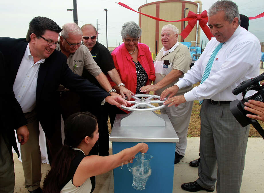San Antonio Water System President and CEO Robert Puente (far right) turns a ceremonial valve Friday July 18, 2014 during the dedication of a SAWS pump station in Schertz, Texas that will bring water to northeast San Antonio from Gonzales County. Photo: JOHN DAVENPORT, San Antonio Express-News / ©San Antonio Express-News/John Davenport