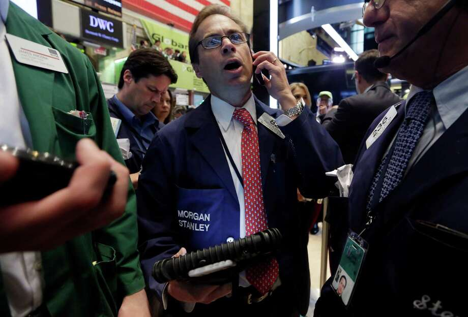 Trader Dudley Devine, center, works on the floor of the New York Stock Exchange, Friday, July 18, 2014. U.S. stocks are opening higher after Google, Honeywell and other big companies report their quarterly results. (AP Photo/Richard Drew) ORG XMIT: NYRD112 Photo: Richard Drew / AP