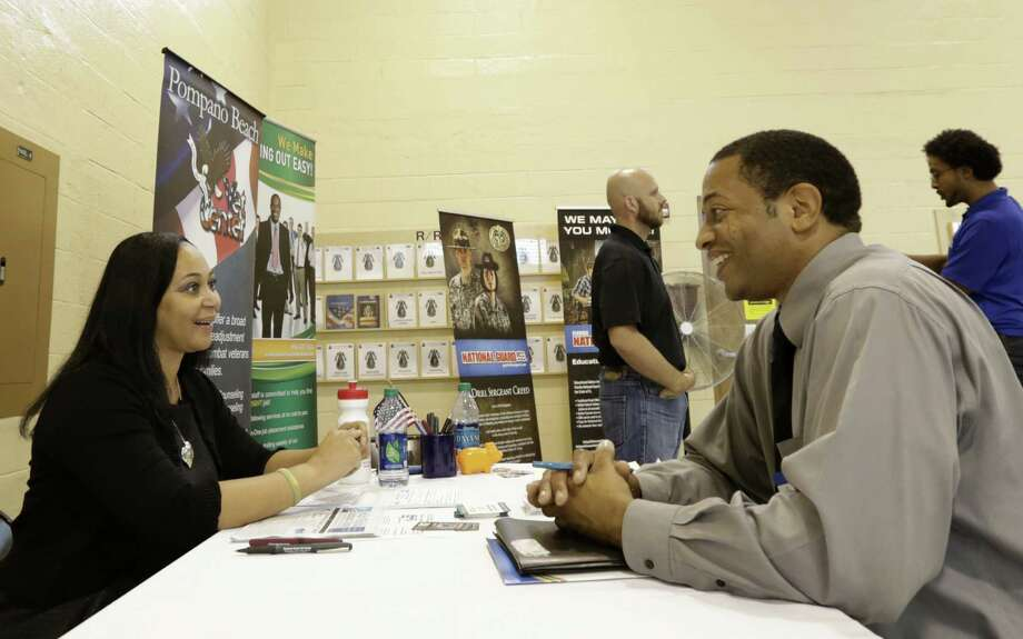 Job seeker and Air Force veteran Jesse Jefferson Jr. talks to Arianna Alexander of the Pompano Beach Veterans Center at a hiring fair in Fort Lauderdale, Fla., on Wednesday. Photo: Alan Diaz / Associated Press / AP