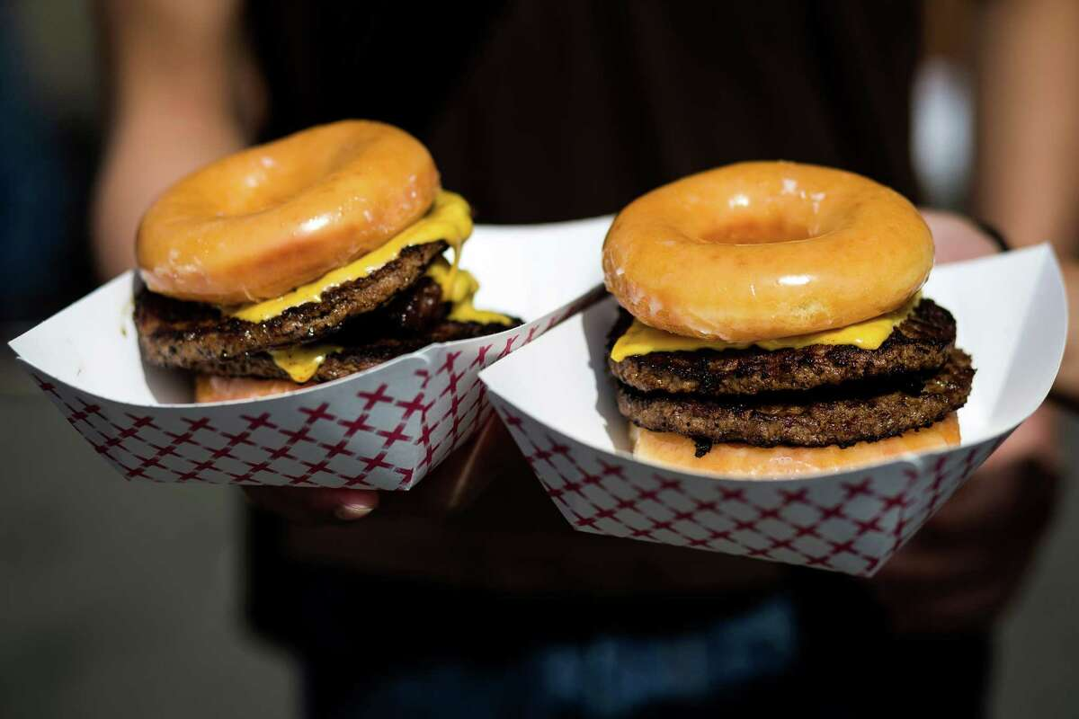 An attendee presents his purchase of two Krispy Kreme bacon cheeseburgers - with buns subbed out for donuts - at the annual Bite of Seattle Friday, July 18, 2014, in Seattle, Wash.