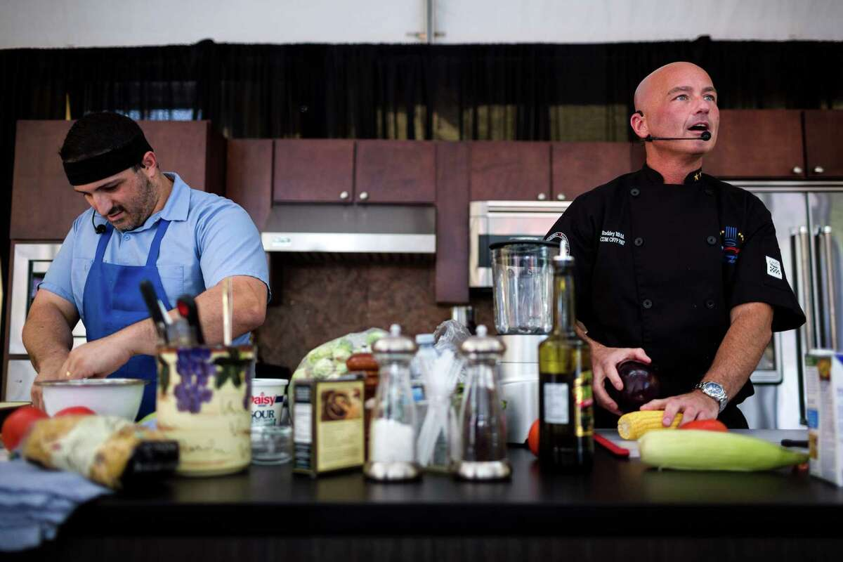Chefs Michael Roddey, right, and Nick Novello , left, go head-to-head during a cook-off at the annual Bite of Seattle Friday, July 18, 2014, in Seattle, Wash.