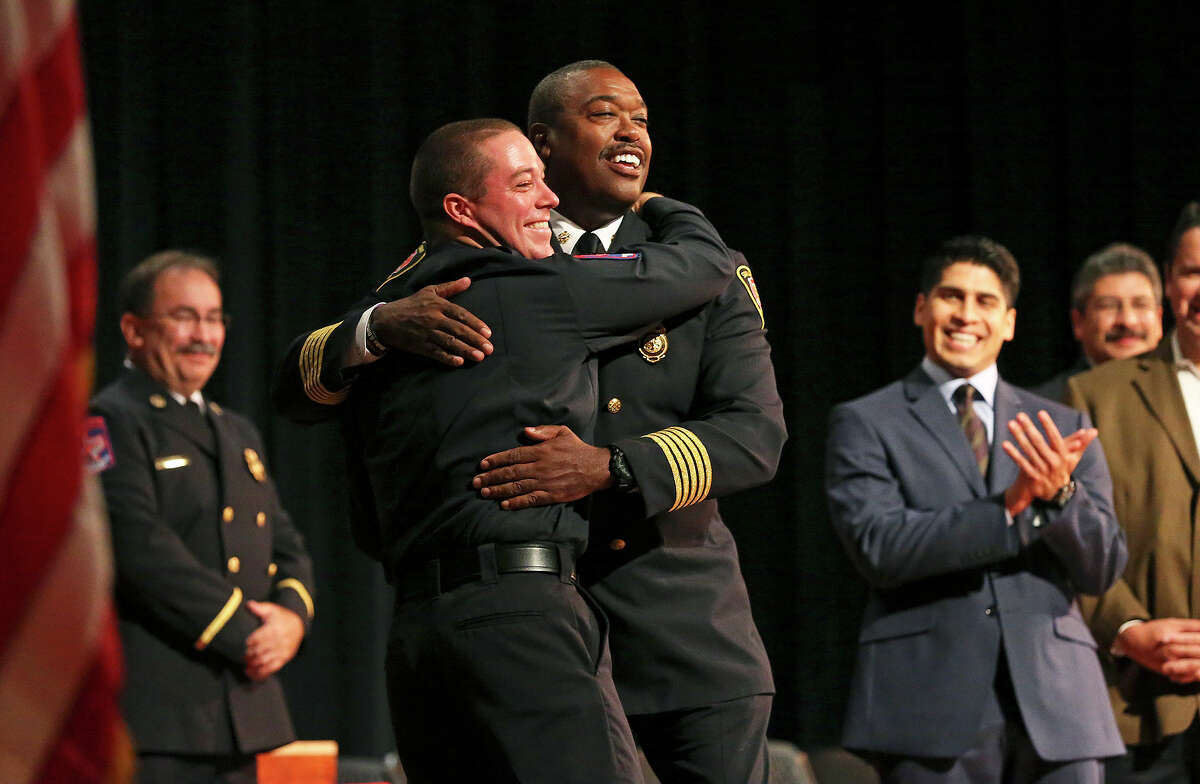 Last to receive his diploma, Christopher Wiley gives a big hug to Fire Chief Charles Hood during the San Antonio Fire Department Cadet Class 2014 Alpha graduation at Antonian College Preparatory High School Auditorium on Friday, July 18, 2014.