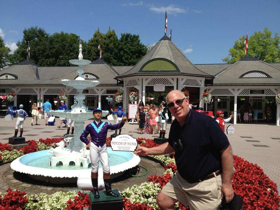 "Ed Stanco had himself quite the summer at Saratoga in 2013. His filly, Princess of Sylmar, won the Coaching Club American Oaks and Alabama. On Opening Day, Stanco, the Schenectady native, was back at the Spa to admire the jockey statues that honor last year's Grade I winners. ""How cool is this?"" Stanco said. (Tim Wilkin / Times Union)"