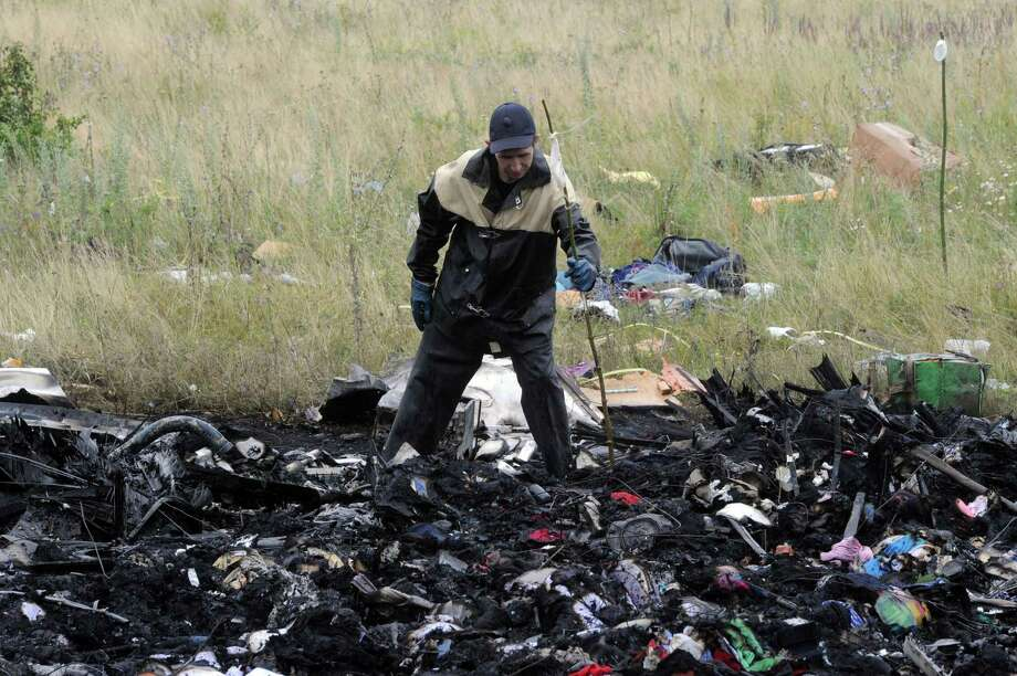 A rescue worker uses sticks to mark the location where bodies of victims have been found at the site of the crash of a Malaysian airliner carrying 298 people from Amsterdam to Kuala Lumpur in Grabove, in rebel-held east Ukraine, on July 18, 2014. Pro-Russian separatists in the region and officials in Kiev blamed each other for the crash, after the plane was apparently hit by a surface-to-air missile. Members of the UN Security Council demanded a full, independent investigation into the apparent shooting down of a Malaysia Airlines jet over Ukraine.  AFP PHOTO / DOMINIQUE FAGETDOMINIQUE FAGET/AFP/Getty Images ORG XMIT: 462 Photo: DOMINIQUE FAGET / AFP