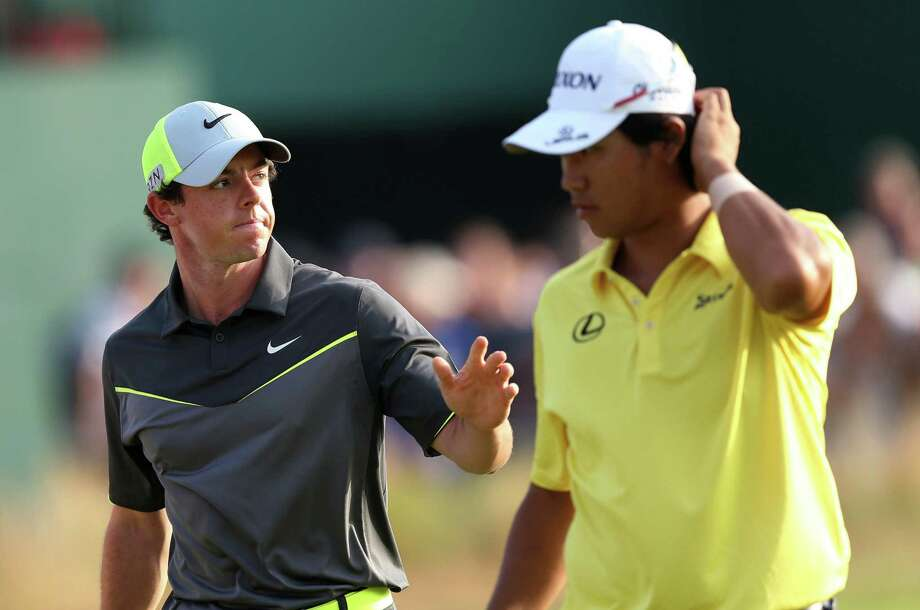 Rory McIlroy (left), walking with Hideki Matsuyama, waves after his second straight 6-under 66 at Royal Liverpool. Photo: Scott Heppell / Associated Press / AP