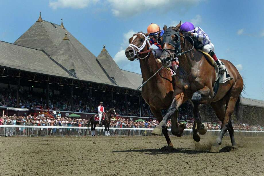 Winter Games, right, with jockey Jose Ortiz out duels Goodnewsisnonews with jockey John Velazquez, left, for the win in the first race of the 2014 Saratoga Race Course meeting Friday afternoon, July 18, 2014, in Saratoga Springs, N.Y.    (Skip Dickstein / Times Union) Photo: SKIP DICKSTEIN