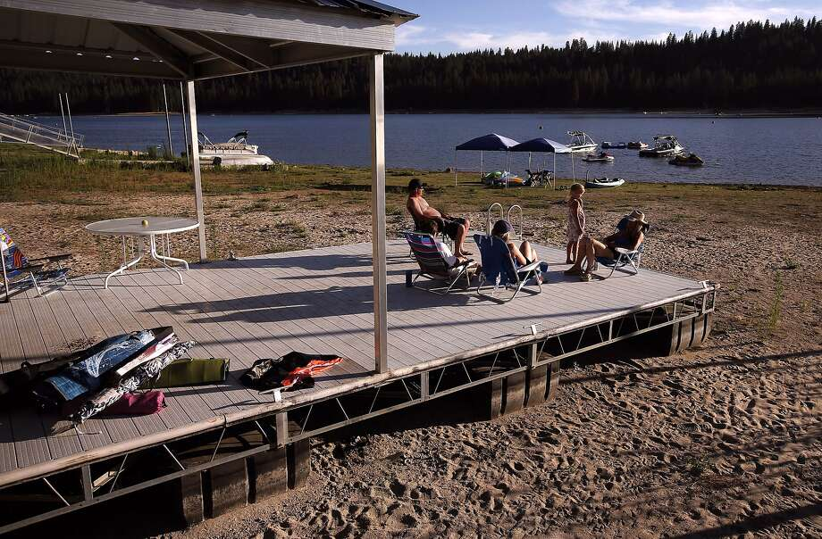 A family and friends make the best of a boat dock that would normally be afloat at Bass Lake near Oakhurst (Madera County). The lake is both a hydroelectric reservoir and recreation area. The loss of hydropower has utilities turning to power plants. Photo: Michael Macor, The Chronicle