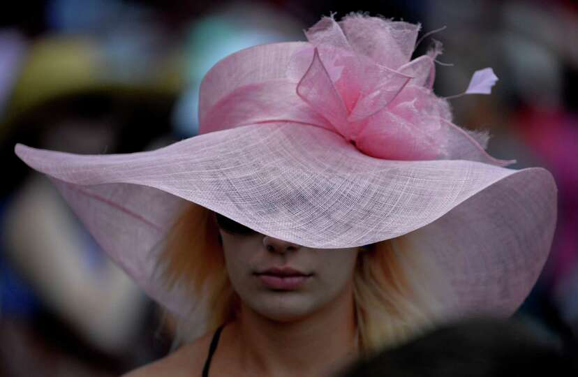 A woman shows of a beautiful pink hat on opening day of the 2014 Saratoga Race Course meeting Friday