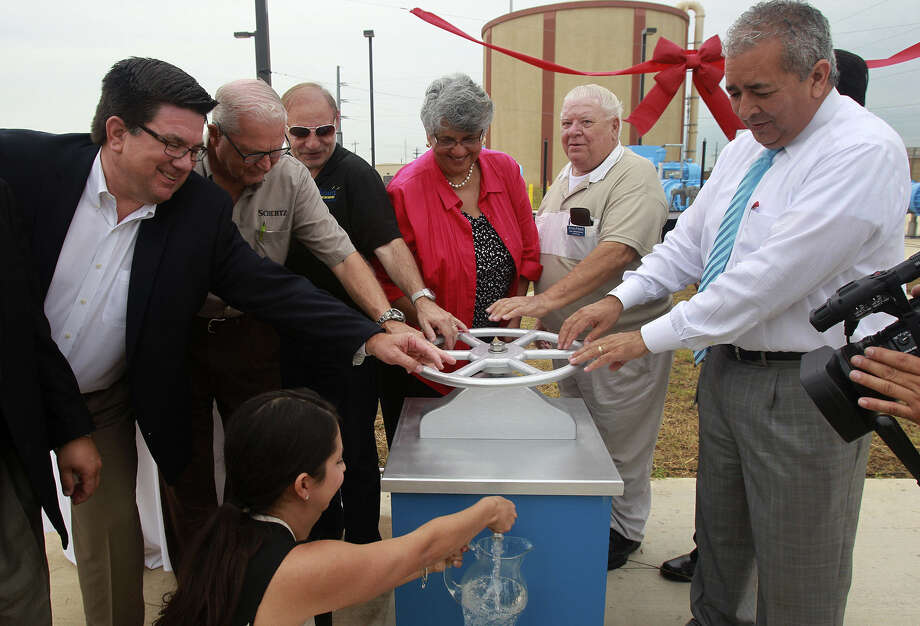 San Antonio Water System President and CEO Robert Puente (far right) turns a ceremonial valve Friday during the dedication of a SAWS pump station in Schertz that will bring water to Northeast San Antonio from Gonzales County.  On the far left is Seguin City Manager Douglas Faseler. Photo: John Davenport / San Antonio Express-News / ©San Antonio Express-News/John Davenport